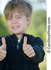 A kid giving a two thumbs up