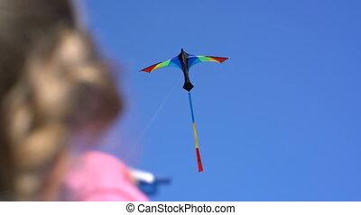 a kite in the sky on a clear day in the girl's hand