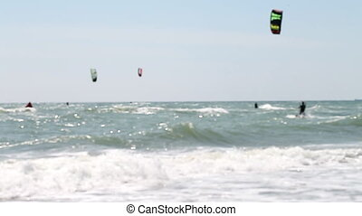 Kitesurfing, a group of athletes riding the waves - a...