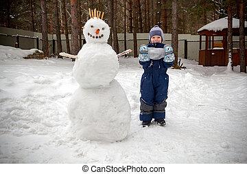 a, kleiner junge, in, der, winter, garten, steht, neben, a, schneemann