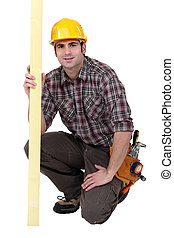 A kneeled male carpenter.