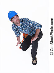 A kneeling construction worker.