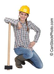 A kneeling tradeswoman