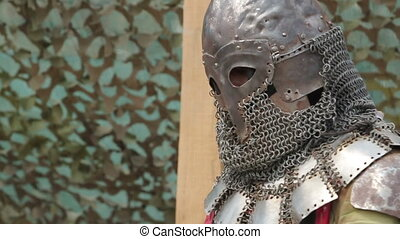a knight in armor and a helmet with a sword