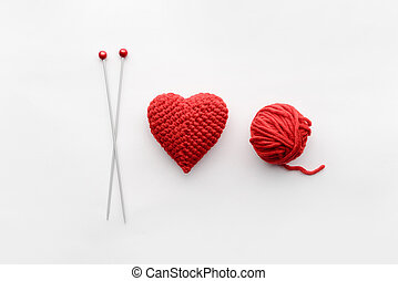 a knitted heart of red thread with an inserted knitting...