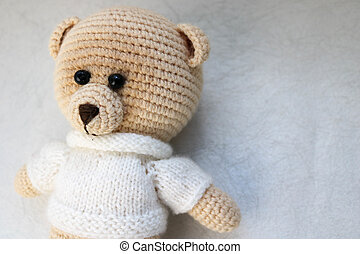 A knitted homemade beautiful cute little bear in a white sweater with black eyes, a soft toy tied with beige large threads on a light white background. The background.
