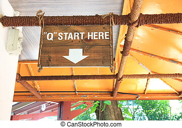 "A label print of ""Q START HERE"""