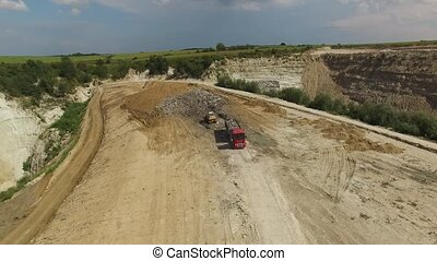 A landfill lorry is preparing for unloading garbage in junkyard. Aerial shot.