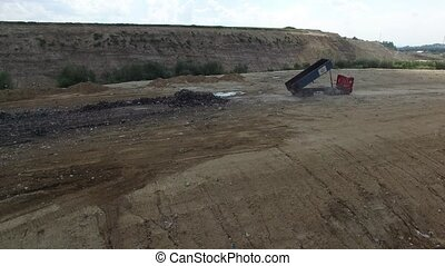 A landfill lorry is unloading garbage into junkyard. Aerial shot.
