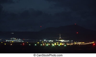 An aircraft landing on a lighted landing strip at a night airport