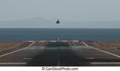 A frontal shot of an airstrip, ending in a sea, and a helicopter, going down and preparing to land