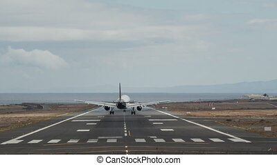 A frontal shot of an airport runway with a landing aircraft from the back