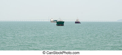 A landscape image of a cargo ship sailing past the Penang Bridge.