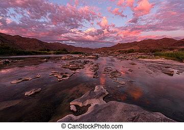 A landscape of a golden pink sunset over the Orange River