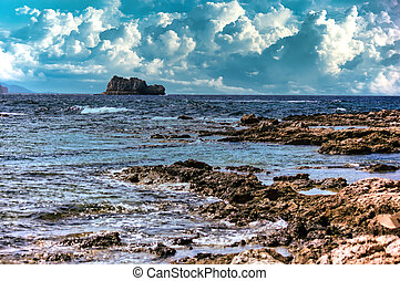 A landscape view across the sea from Imeri Gramvousa to Cape Gramvousa, Kissamos, Crete, Greece against dramatic clouds and rocky terrain