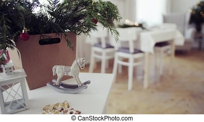A lantern and a rocking horse on a table at home at...