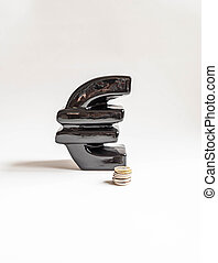 A large black ceramic piggy bank in the form of a euro and and a stack of coins on a white background. Copy space