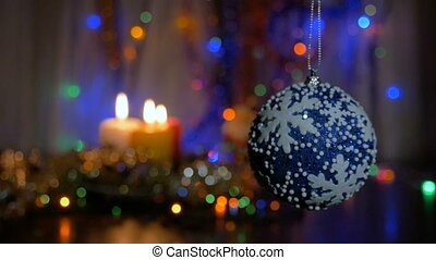 A large blue ball hangs on the Christmas tree. Blurred background