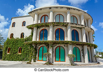 A large building with columns overgrown with ivy. Mexico, Quintana Roo.