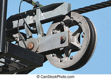 A large cable pulley system used to run a ski lift. Set against a clear blue sky.
