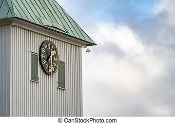 A large clock mounted to the side of a church building in Kungalv