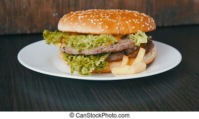A large delicious juicy burger with triple cutlet, fresh lettuce leaf and cheese lies on a white plate on a stylish wooden background