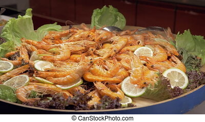 A large dish full of cooked shrimps with lemon and lettuce...