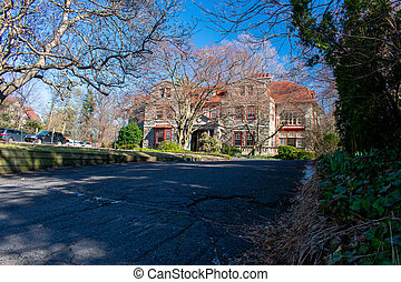 A Large Estate Like Property With a Large Driveway on a Blue Sky