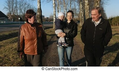 A large family walks in the park near the road at sunset. Grandmother and grandfather are talk with their grandson and daughter