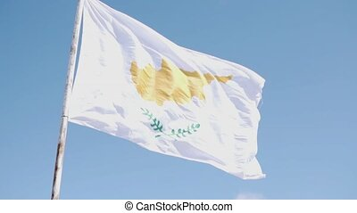 A large flag of Cyprus is being developed against a blue sky