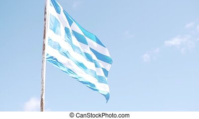 A large flag of Greece develops against a blue sky