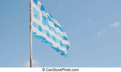 A large flag of Greece flutters in the wind against the sky with white clouds
