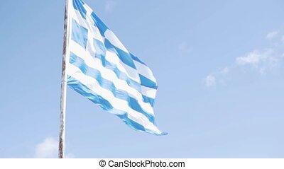 A large flag of Greece flutters in the wind against the sky with white clouds.