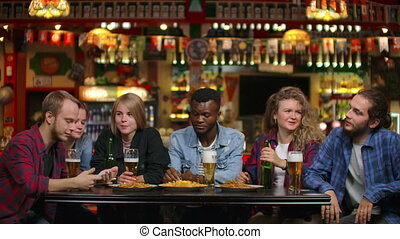 A large group of friends in the bar sitting at the table laughing and chatting drinking beer