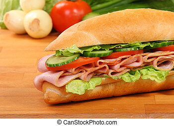 A large ham and tomato sandwich, on a wooden board