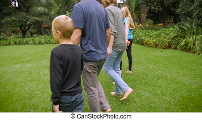 A large happy family holding hands while walking in the grass - slowmo steadicam