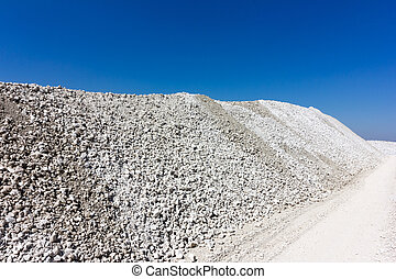 a large mound of crushed stone limestone against the blue sky