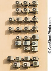 a large number of air conditioners on the brown wall