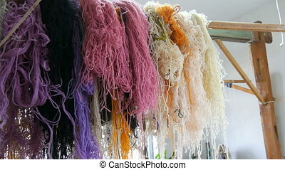 A large number of different woolen threads. Handmade carpet embroidery.