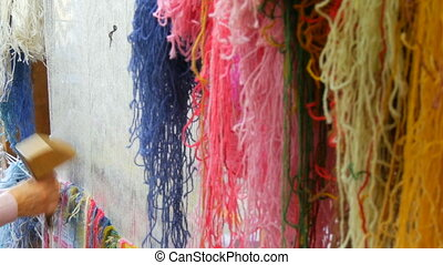 A large number of different woolen threads. Handmade carpet embroidery. Women's hands create a pattern using multi-colored threads. Hammer for embroidery quors, stuffing threads.