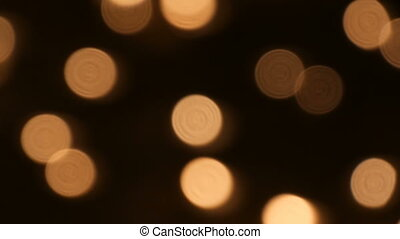 A large number of small blurred white round candles burning...