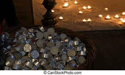 A large number of small round wax candles that lie in a...