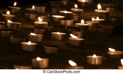 A large number of small white round candles burning in the...