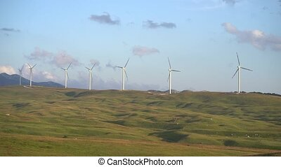 A large number of wind turbines stand in the field at sunset, a skyline with blue sky and velvet clouds.
