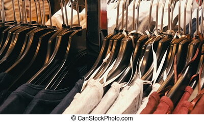 A large number of women's clothing of different colors hangs...
