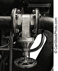 a large old metal industrial valve with round handle mounted on a large black machine with bolts and shiny pipes