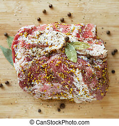 A large piece of fatty pork meat marinated with mustard, pepper and various condiments
