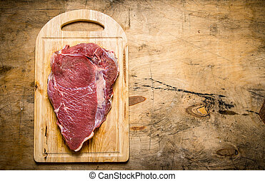 A large piece of raw fresh meat on cutting Board.