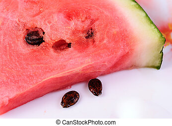 A large piece of watermelon on a plate with two seeds