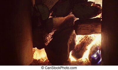 A large pile of firewood, burning in a brick fireplace, the flames of flame burst up, real firewood, very warm.